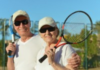 Happy elderly couple with tennis racket in hand